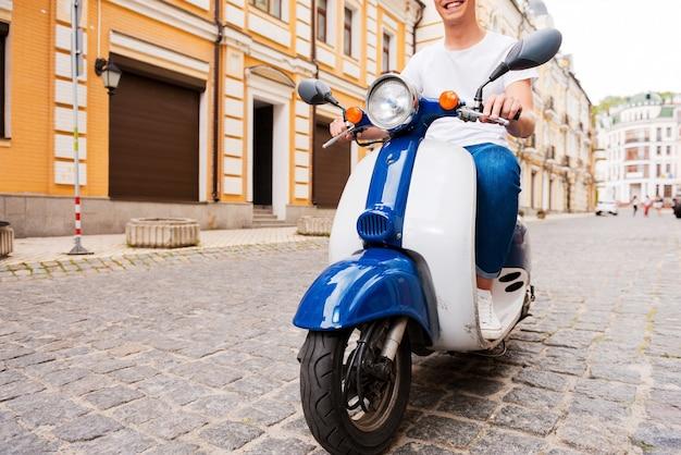 Jazda z przyjemnością. przycięty obraz szczęśliwego młodego mężczyzny jadącego skuterem wzdłuż ulicy