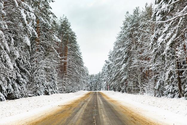 Jazda zimą - curvy snowy country road - kręta zaśnieżona wiejska droga prowadząca przez górski krajobraz.