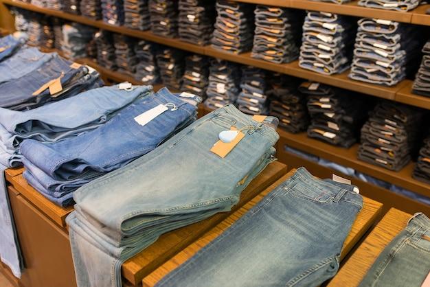 Jeansy męskie składane na półce w sklepie odzieżowym