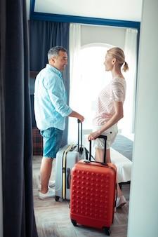 Jechać na wakacje. uśmiechnięty mąż i żona trzymający walizki podróżne przed wyjściem z domu.