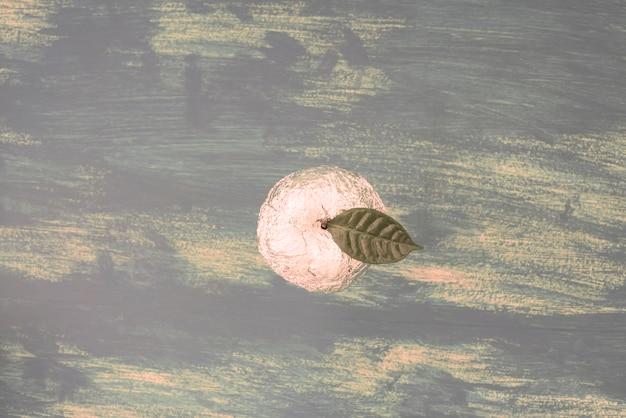 Jeden apple na niebieskim tle shabby w folii zawinięte w zielony liść.