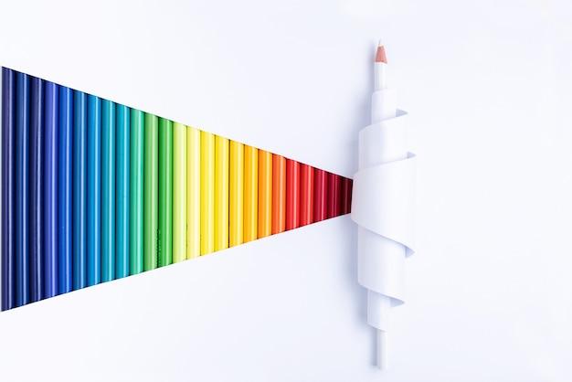 Jeden biały ołówek zwinięty w zwinięty papier z kolorowymi kredkami.