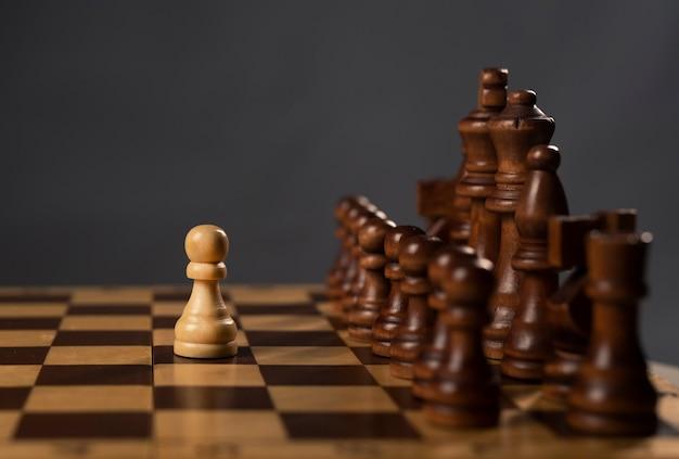 Jeden biały pionek przeciwko grupie czarnych figur szachowych na szachownicy