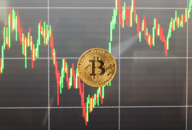 Jeden bitcoin z wykresem w tle