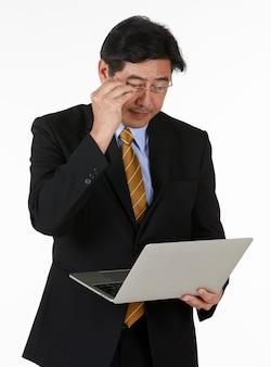 Jeden biznesmen w czarnym formalnym garniturze stoją dotykając okularów i patrzą na notatnik w ręku. studio strzelać pół ciała z białym tłem. koncepcja inwestycji, nowości, technologii, przyszłości.