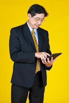Jeden biznesmen w czarnym garniturze formalnym stoją dotykając okularów i patrzą na tablet w ręku. studio strzelać pół ciała z białym tłem. koncepcja inwestycji, nowości, technologii, przyszłości.
