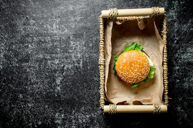 Jeden burger w koszyku. na czarnym tle rustykalnym
