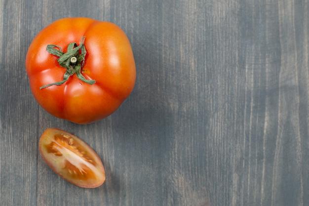 Jeden cały soczysty pomidor na drewnianym stole