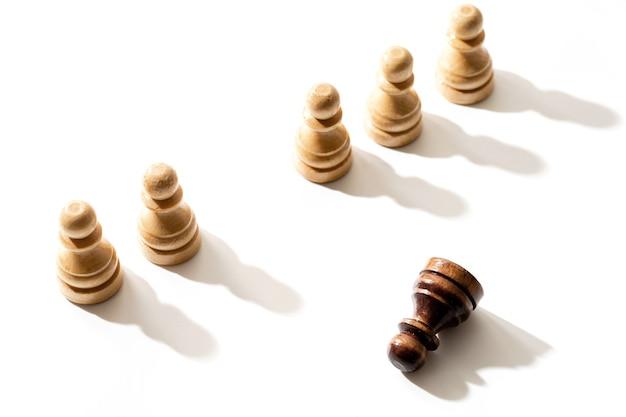 Jeden czarny pionek szachowy leżący wśród białych. pojęcie rasizmu i dyskryminacji.