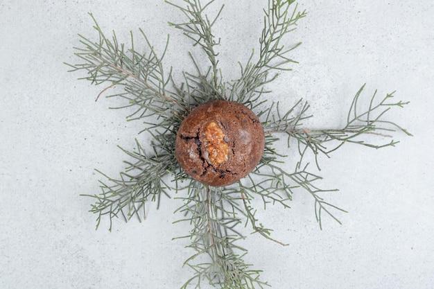 Jeden czekoladowy plik cookie z orzechami na białej powierzchni.