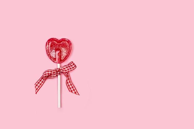 Jeden czerwony lizak w kształcie serca na różowym tle