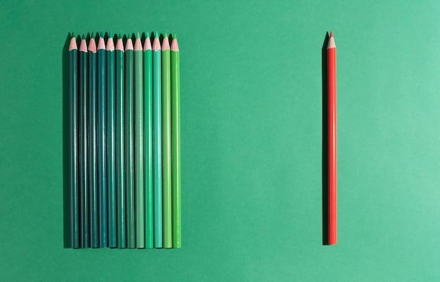 Jeden czerwony ołówek leży przed kilkoma zielonymi ołówkami na zielonym tle.