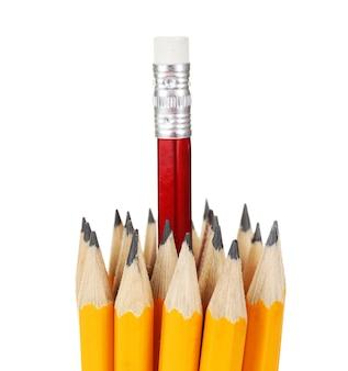 Jeden czerwony ołówek wyróżniający się od innych, na białym tle