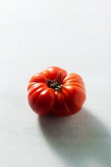 Jeden czerwony pomidor na stole. światło od tyłu. oxheart