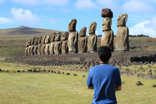 Jeden człowiek podziwia olbrzymie posągi moai ahu tongariki, wyspy wielkanocnej, chile, ameryki południowej