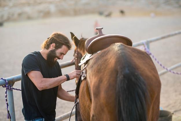 Jeden człowiek sam na ranczo opiekujący się koniem - uśmiechnięty i dobrze się bawiący naprawianie - koń gotowy do biegu i gotowy do wyjazdu ze swoim kowbojem
