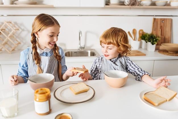Jeden dla ciebie. żywa, troskliwa ładna dziewczyna daje swojemu młodszemu bratu kawałek chleba z masłem orzechowym, podczas gdy oboje siedzą rano przy stole i jedzą razem śniadanie