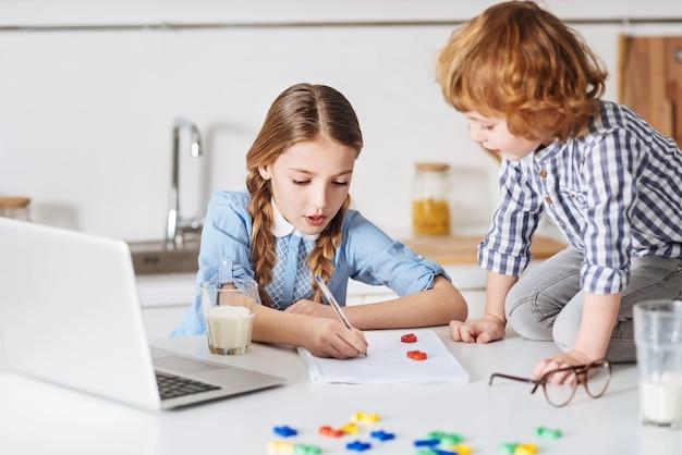 Jeden dodać jeden. produktywna piękna młoda dama używa specjalnej gry do nauczania matematyki swojego rodzeństwa, spędzając z nim czas w domu