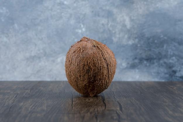 Jeden dojrzały cały orzech kokosowy umieszczony na drewnianym.