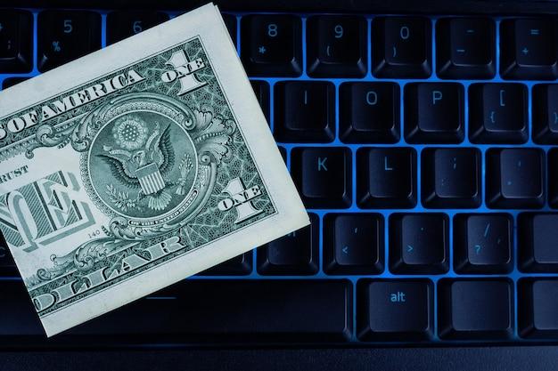 Jeden dolar leży na czarnej podświetlanej klawiaturze, tle dolara i klawiatury, koncepcja biznesowa
