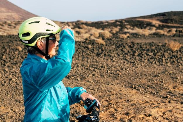 Jeden dorosły i starszy w skalistej górze jeżdżący na rowerze podczas ćwiczeń - aktywna dojrzała kobieta wykonuje aktywność i patrzy na horyzont