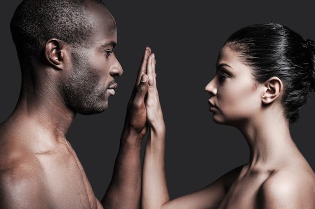 Jeden dotyk i jedna miłość. portret bez koszuli afrykańskiego mężczyzny i kaukaskiej kobiety trzymających się za ręce i patrzących na kamerę, stojąc na szarym tle