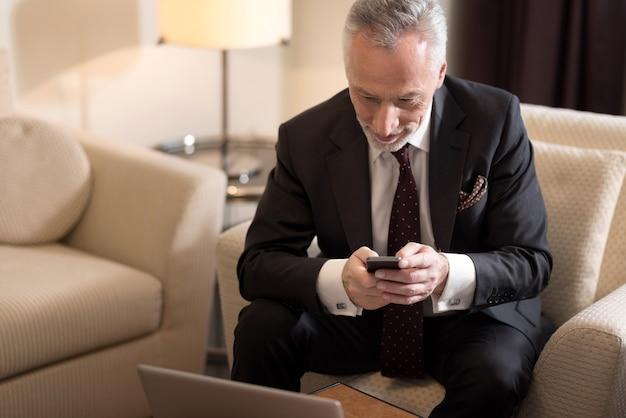 Jeden dotyk. uśmiechnięty wesoły biznesmen w wieku trzymający telefon i siedzący w hotelu przed laptopem podczas pracy nad projektem i wyrażania podekscytowania