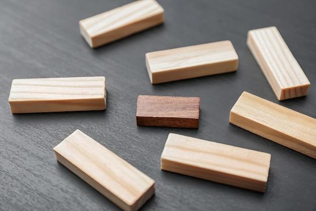 Jeden drewniany klocek wyróżniający się spośród innych w ciemności. pomyśl o innej koncepcji