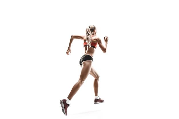Jeden kaukaski kobiece sylwetka biegacza bieganie i skakanie na tle białego studia. sprinter, jogger, ćwiczenia, trening, fitness, trening, koncepcja joggingu.