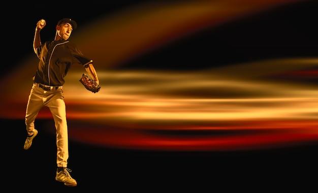 Jeden kaukaski mężczyzna jako baseballista grający na ciemnym tle neonu. model męski jako dzban. pojęcie fitness, ćwiczenia, sport, zdrowy styl życia, ruch lub ruch. kreatywny kolaż.