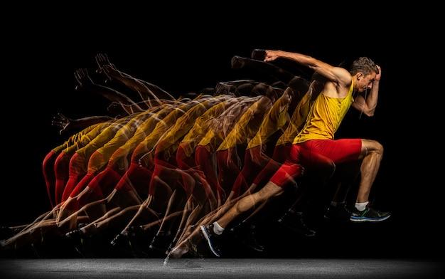 Jeden kaukaski profesjonalny mężczyzna sportowiec, trening biegacz na białym tle na ciemnym tle studio.