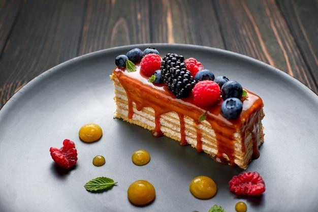 Jeden kawałek ciasta miodowego ze świeżymi jagodami, miętą i karmelem, na drewnianym stole