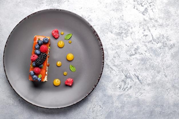 Jeden kawałek ciasta miodowego ze świeżymi jagodami, miętą i karmelem