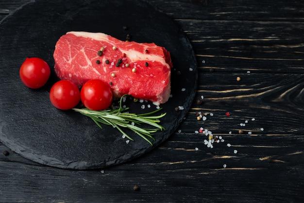 Jeden kawałek soczystej surowej wołowiny na kamiennej desce do krojenia na czarnym drewnianym stole.