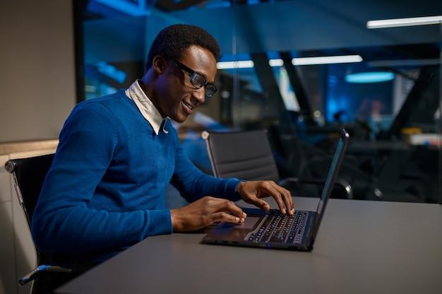 Jeden kierownik w okularach pracuje na laptopie w nocnym biurze. mężczyzna pracownik, ciemne wnętrze centrum biznesowego, nowoczesne miejsce pracy