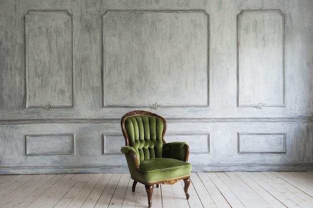 Jeden klasyczny fotel przy białej ścianie i podłodze. skopiuj miejsce