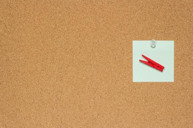 Jeden kolorowa notatka z białymi pushpins i clothespins odizolowywającymi na korkowym tle