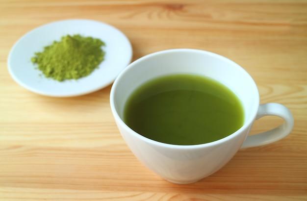 Jeden kubek tętniącego życiem koloru gorącej zielonej herbaty matcha z niewyraźnym proszkiem herbaty matcha w tle