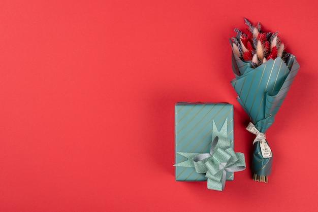 Jeden mały bukiet lawendy z lagurusem i prezentem w turkusowym opakowaniu na czerwonym tle.