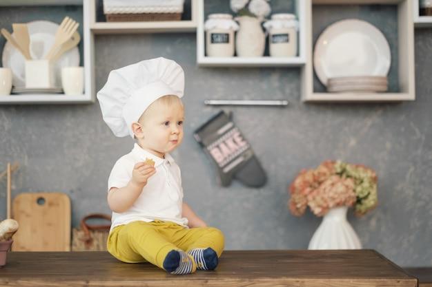 Jeden mały chłopiec w kapeluszu szefa kuchni w kuchni siedzi na stole i je