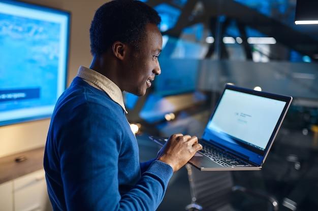 Jeden menedżer pracuje na laptopie w nocnym biurze. mężczyzna robotnik, ciemne wnętrze centrum biznesowego, nowoczesne miejsce pracy