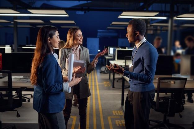 Jeden mężczyzna i dwie kobiety rozmawiają w nocnym biurze. uśmiechnięci pracownicy płci męskiej i żeńskiej, ciemne wnętrze centrum biznesowego, nowoczesne miejsce pracy
