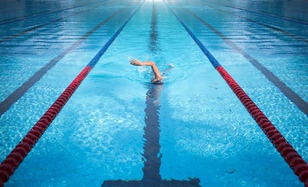 Jeden mężczyzna płynie po pasie basenowym