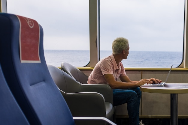 Jeden młody człowiek używający swojego laptopa lub komputera pc na statku płynącym po wodzie morza lub oceanu - mężczyzna patrzący na zewnątrz podczas pracy z urządzeniem - na białym tle nomada samotnie podróżujący