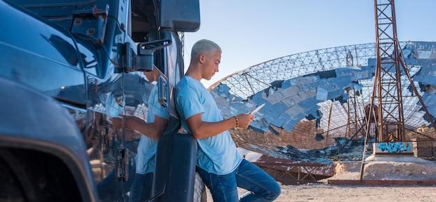 Jeden młody mężczyzna trzymający i używający tabletu lub telefonu sam w szczerym polu ze swoim samochodem - przy użyciu koncepcji technologii i stylu życia - nastolatek i milenial