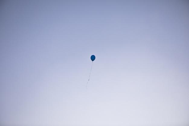 Jeden niebieski balon wypełniony helem na tle błękitnego nieba.