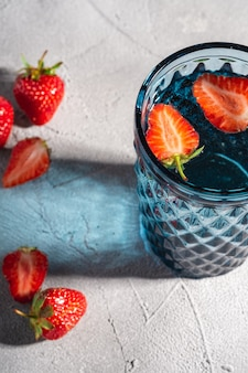 Jeden niebieski geometryczny szklany kubek ze świeżą wodą i owocami truskawek z kolorowymi promieniami światła cienia na kamieniu