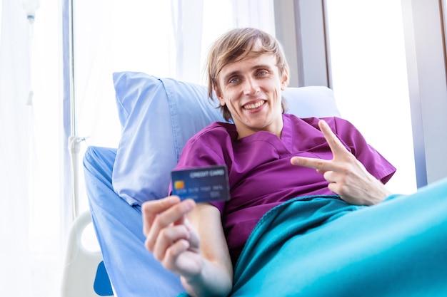 Jeden pacjent mężczyzna na wystawie trzymający kartę kredytową leżącą z windami dwa palce w górę, walczący na łóżku w tle szpitala w pokoju, koncepcja leczenia płatności