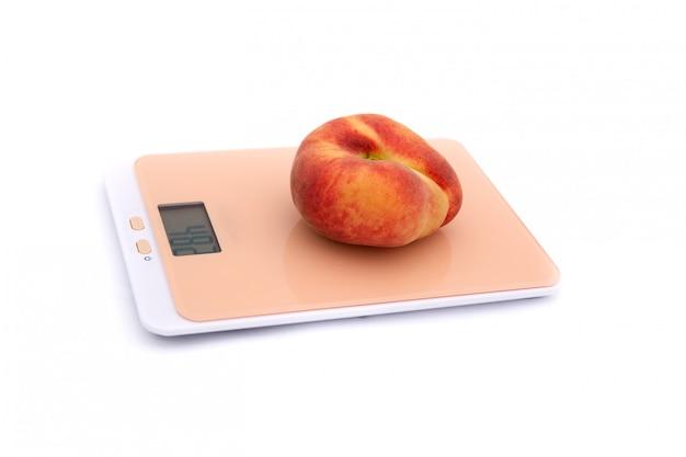 Jeden płaski brzoskwinie na wadze kuchennej na białym tle
