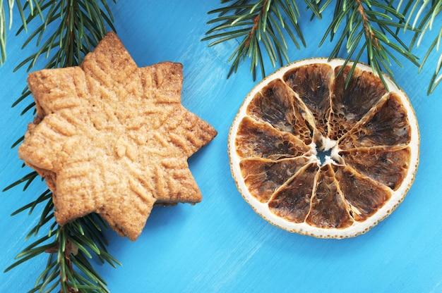 Jeden plik cookie w postaci płatków śniegu i suszonych pomarańczy na niebieskim tle drewnianych